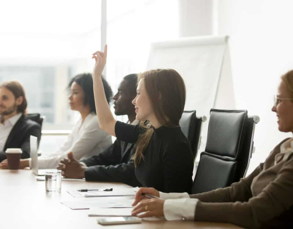 Smiling curious businesswoman raising hand at group meeting