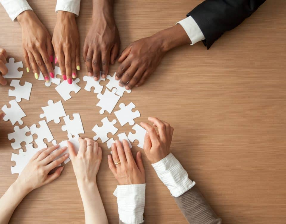 Hands of multi-ethnic business team assembling jigsaw puzzle